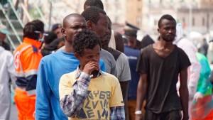 A líbiai partoktól fahajóval útnak indult migránsok hagyják el a Siem Pilot norvég vontatóhajó fedélzetét a dél-olaszországi Salerno kikötőjében. (MTI/EPA/Cesare Abbate)