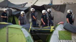 Követ dobáló bevándorlókkal állnak szemben görög rendőrök. (MTI/AP/Darko Bandic)