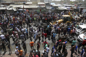 A roncsokat takarítják Bagdadban, a robbantás helyszínén Fotó: Hálid Mohammed
